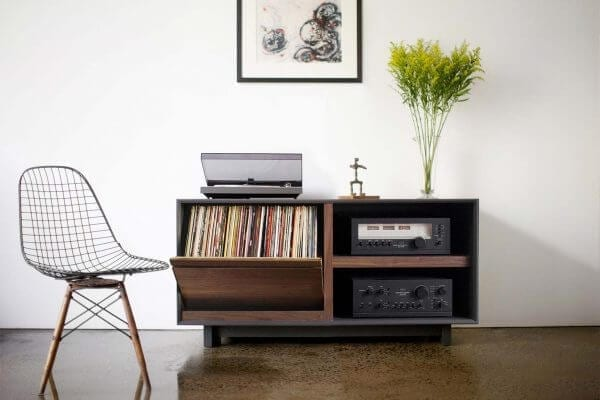 AERO 51 LP Storage Console made from North American hardwood. Features a flip-style record storage bins with room for 120 LPs. The right side drawers have room for hi-fi audio equipment. It features a Walnut finish and is sitting in a living room setting.