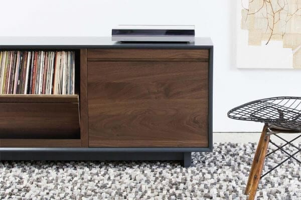 AERO 51 LP Storage Console made from North American hardwood. Features 2 flip-style record storage bins with room for 120 LPs. It features a Walnut finish and a Modern Record Player sits on top. The storage cabinet is sitting in a living room setting.