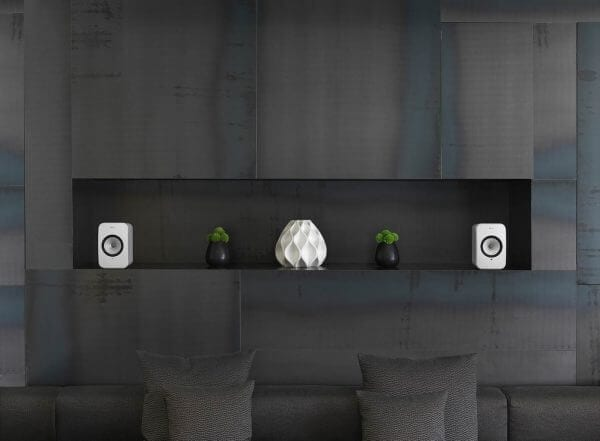 KEF LSX white dual wireless power speakers in black-themed living space setting.