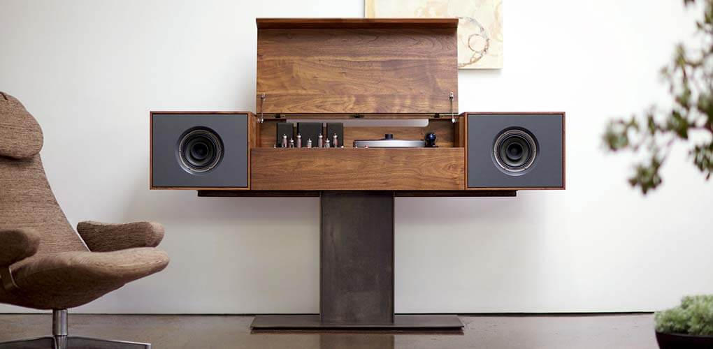 Modern Record Console with full-range alnico drivers and wireless BlueTooth streaming in a living room setting. The stereo console has its premium North American wood cover pulled up displaying an integrated high-tech turntable and hand-built tube amplifier.