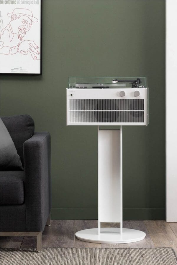 Modern Record Player with the bright white exterior on sturdy record player stand to create high-fidelity sound with a custom hand-built amplifier in a living room setting.