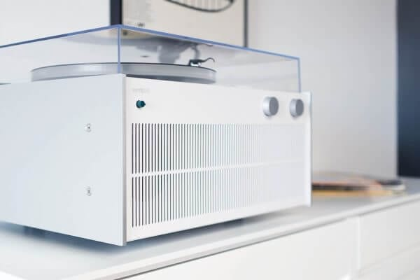 Modern Record Player with a bright white exterior that creates high-fidelity sound with a custom hand-built amplifier sitting on a bright white record storage cabinet.