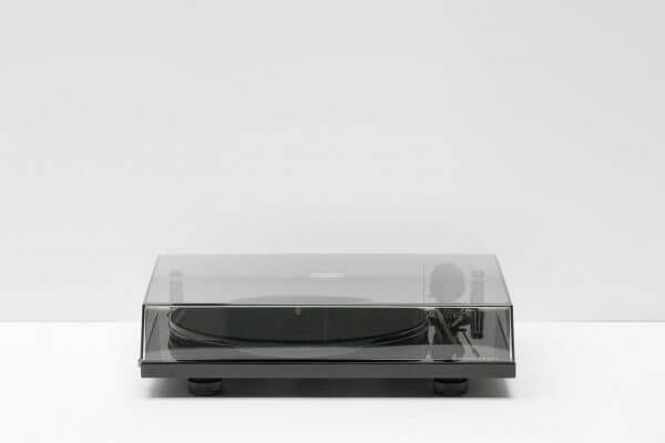 Pro-Ject Debut Carbon DC Turntable with a closed overhead clear cover. 6th Generation Hi-Fi classic stainless steel in a dark black theme. It stands at 16.3 inches tall and 4.6 inches wide.
