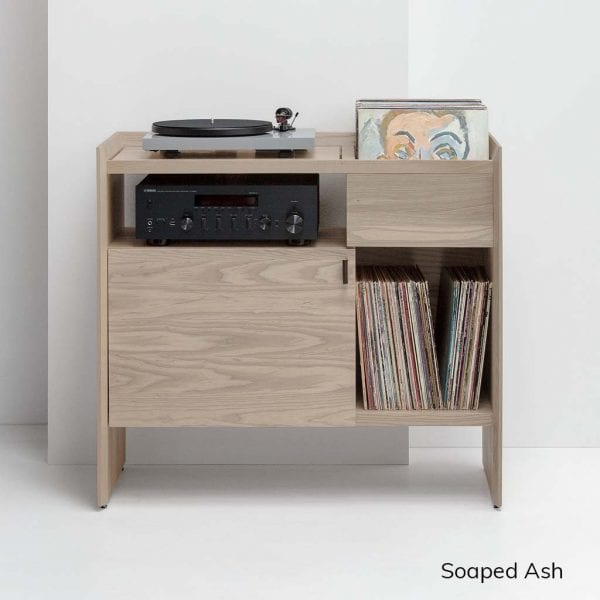 Unison Record Player Stand in Soaped Ash comes in a light white finish and features a vibration isolated turntable platform, ample LP storage space, and premium leather door pulls. Stores up to 165 records and includes adjustable levelers for uneven floors. It stands at 38 inches wide, 18 inches deep, and 34 inches tall.