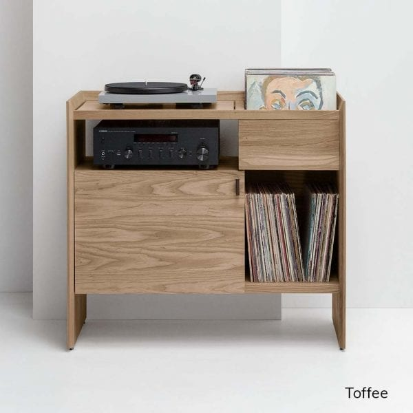 Unison Record Player Stand in Toffee features a light and rich finish. The Unison Record Player features a vibration isolated turntable platform, ample LP storage space, and premium leather door pulls. Stores up to 165 records and includes adjustable levelers for uneven floors. It stands at 38 inches wide, 18 inches deep, and 34 inches tall.