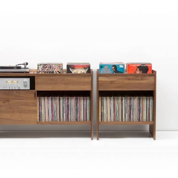 Unison Record Storage Stand with flip-style LP storage bins, vibration isolated record player platform, and audio cabinet room for hi-fi sound equipment. Standing next to a Unison Vinyl Storage Cabinet with rich walnut finish. Crafted from premium North American hardwoods and focused on premium vinyl storage.